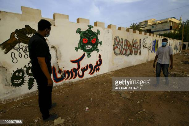 Sudanese volunteers, wearing protective face masks, stand next to a graffiti of the COVID-19 virus in the capital Khartoum on April 8 as they clean a...