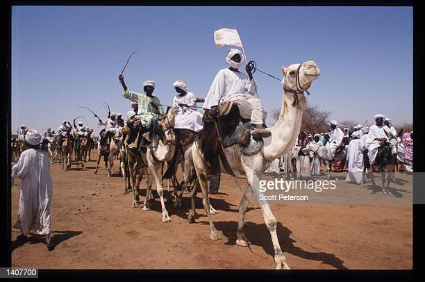 Sudanese warriors participate in a rally for President Omar Hassan el-Bashir February 28, 1992 in Ed Daein, Sudan. Upon his return from a development...