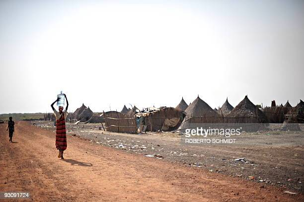 STORY SOUTH SUDAN ON THE OLD 'BLOOD ROUTE' THE CURSE OF BLACK GOLD BY HERVE BAR A Sudanese woman carries a jug of water on her head as she heads to...