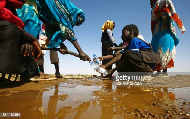 Sudanese woman fills water bottles held by a young boy about 60 kilometres north of ElFasher the capital of the North Darfur state on February 9 2017...