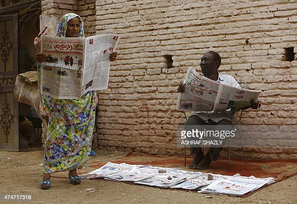 A Sudanese woman holds a newspaper next to a street vendor in a street in AlJarif city outside the capital Khartoum on May 25 2015 Sudanese security...