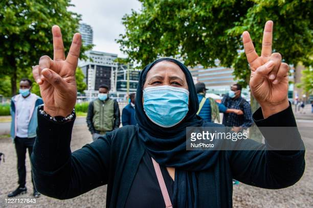 Sudanese woman is making the peace symbol, during the demonstration against the deportations back to Sudan, in The Hague, Netherlands on July 14th,...