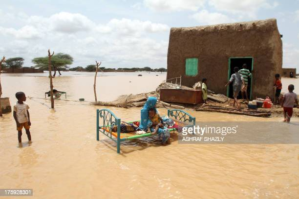 Sudanese woman sits with her child next to her house in a flooded street on the outskirts of the capital Khartoum on August 10, 2013. Drainage is...