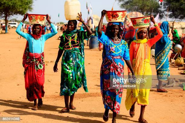 Sudanese women carry buckets and containers of water on their heads in the town of Umm alQura northwest of Nyala in South Darfur province on...