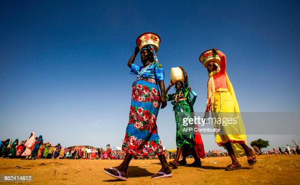 Sudanese women carry buckets and containers of water on their heads in the town of Umm al-Qura, northwest of Nyala in South Darfur province, on...