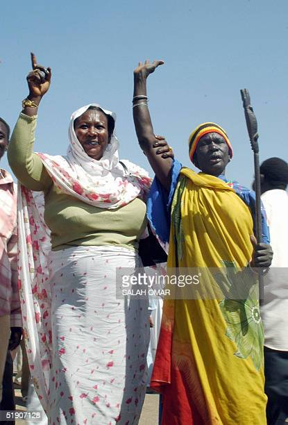 Sudanese women one from the north and one from the south hold hands as they chant 'sawa sawa' during celebrations at the headquarters of the ruling...