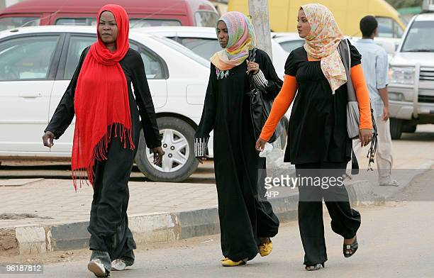 Sudanese women one of them wearing trousers under a long black dress walk in downtown Khartoum on September 8 as a Sudanese female journalist who...