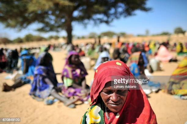 Sudanese women sit and await food and nonfood items being distributed by international humanitarian organizations in the village of Silea which was...