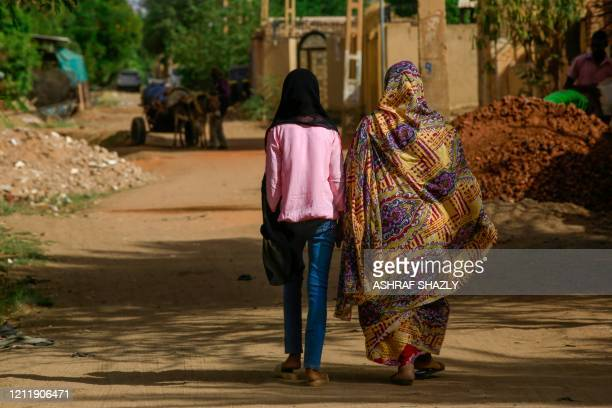 Sudanese women walk in the capital Khartoum's district of Jureif Ghar on May 5, 2020. - Sudan's cabinet approved amendments to the criminal code that...