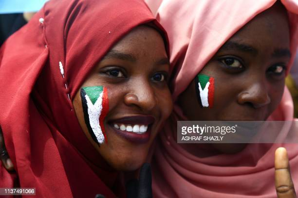 TOPSHOT Sudanese women with national flags painted on their faces take part in a rally in the area of the military headquarters in the capital...