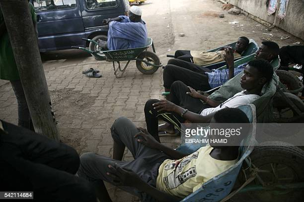 Sudanese workers rest in wheelbarrows in the Sudanese capital Khartoum on June 21 2016 during a hot summer day as Muslims mark the holy fasting month...
