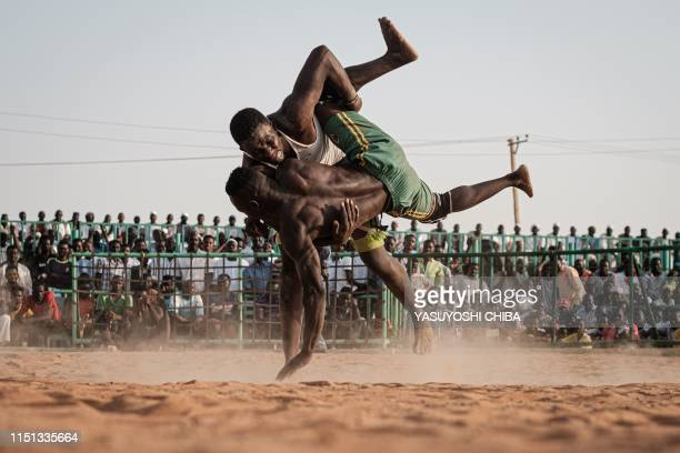 TOPSHOT Sudanese wrestlers fight during a traditional Nuba wrestling match at the Haj Youssef stadium in the district of Khartoum on June 21 2019...