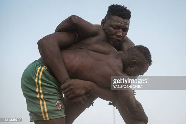 Sudanese wrestlers fight during a traditional Nuba wrestling match at the Haj Youssef stadium in the district of Khartoum on June 21 2019 Originating...