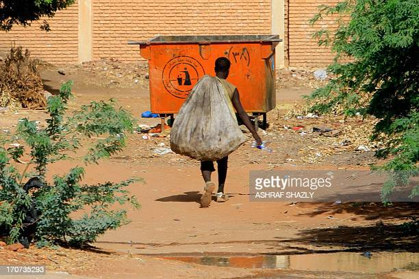 Sudanese youth walks with a sack filled with items collected from garbage containers in Khartoum on June 14 2013 An increasing number of Sudanese are...