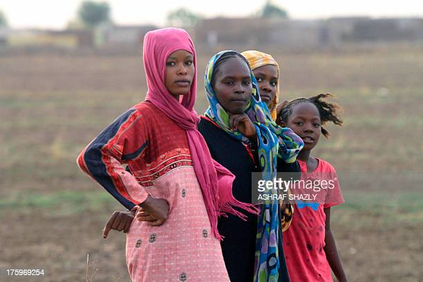 TIMBERLAKE Sudani stand on a field where they cultivate rice as part of the Japanesebacked Gezira rice programme on July 25 2013 in Wad Medani south...