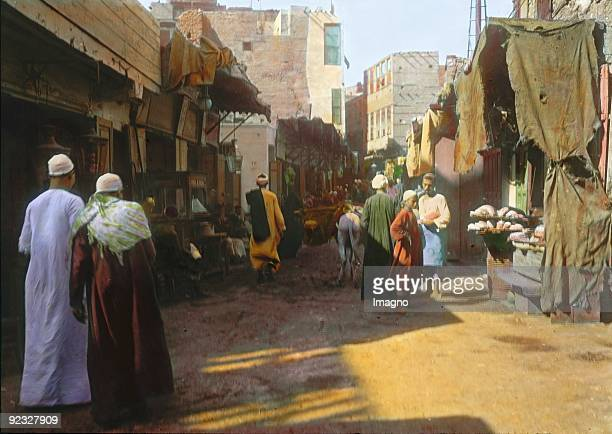Sudanmerchant in a street in the Souq Cairo Egypt Handcolored lantern slide Around 1910