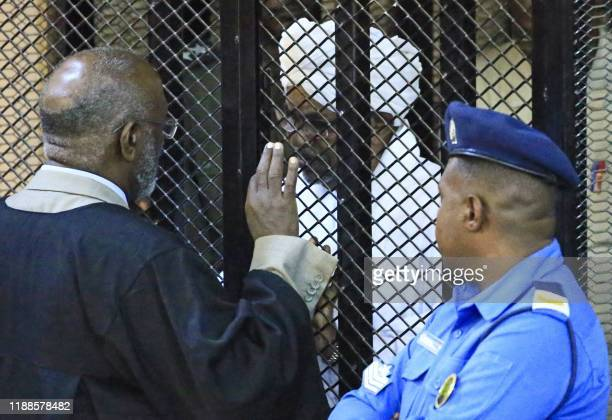 TOPSHOT Sudan's deposed military president Omar alBashir sits in a defendant's cage during his corruption trial at a court in Khartoum on December 14...