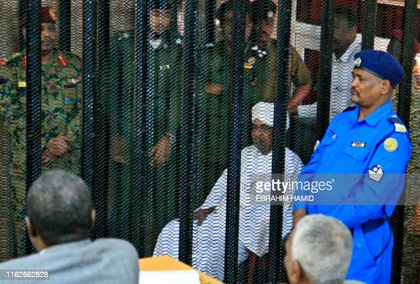 Sudan's deposed military ruler Omar alBashir sits in a defendant's cage during the opening of his corruption trial in Khartoum on August 19 2019...