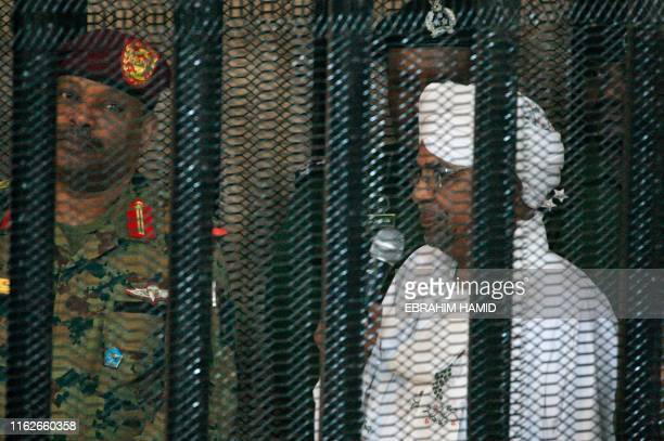 TOPSHOT Sudan's deposed military ruler Omar alBashir stands in a defendant's cage during the opening of his corruption trial in Khartoum on August 19...