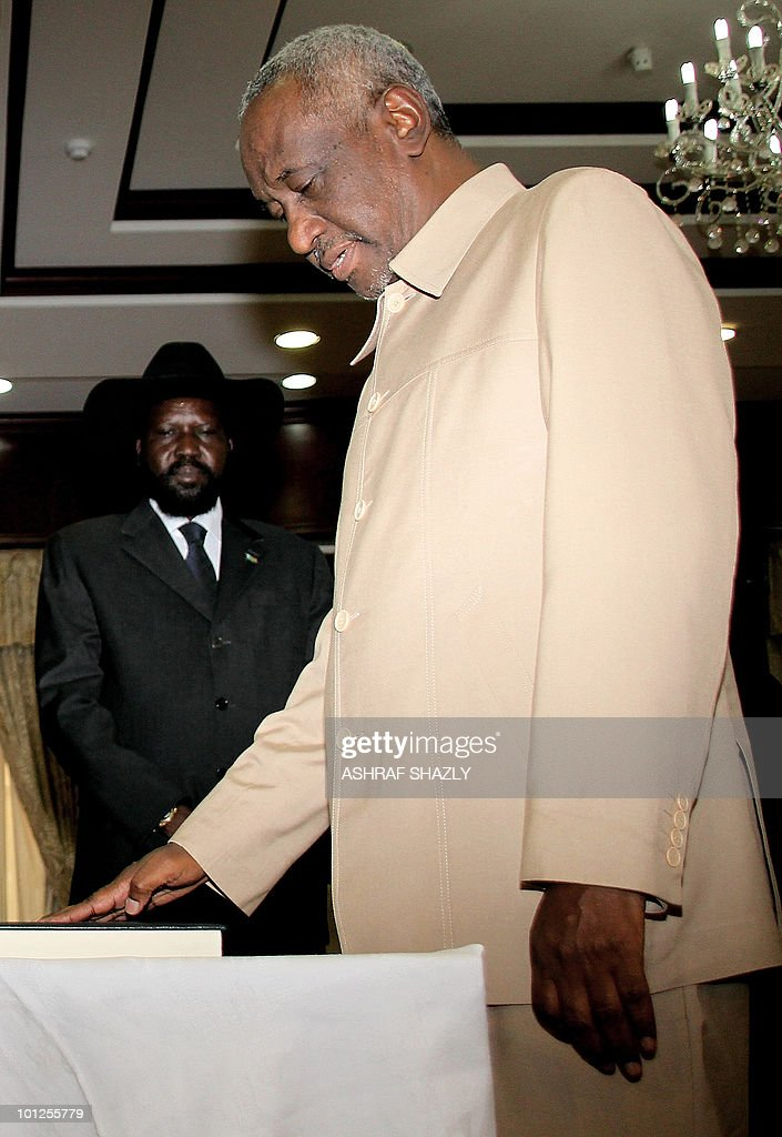 Sudan's First Vice President Salva Kiir, who heads Sudan's former rebel SPLM, looks on as Second Vice President Ali Osman Taha (R) swears on the Koran in front of veteran Sudanese President Omar al-Beshir (not seen in picture) during a swearing in ceremony at the persidential palace in Khartoum on May 29, 2010.