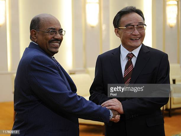 Sudan's leader Omar alBashir shakes hands with China's Chairman of the Standing Committee of the National People's Congress Wu Bangguo during their...