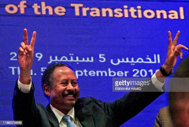 Sudan's new Prime Minister Abdalla Hamdok flashes the victory gesture during a press conference unveiling the first cabinet since veteran leader Omar...