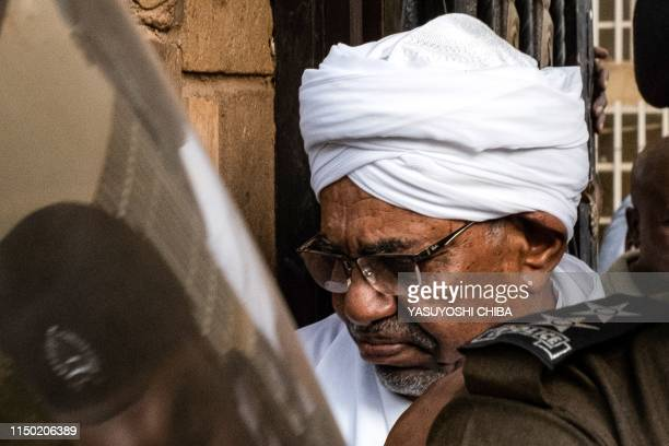 Sudan's ousted president Omar alBashir is escorted into a vehicle as he returns to prison following his appearance before prosecutors over charges of...