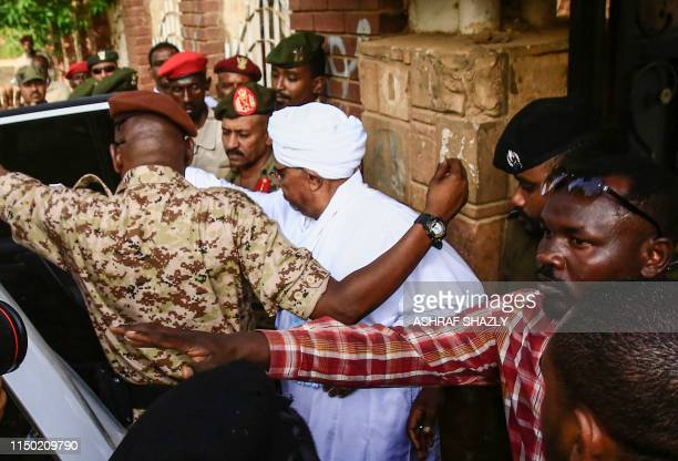 TOPSHOT Sudan's ousted president Omar alBashir is escorted into a vehicle as he returns to prison following his appearance before prosecutors over...