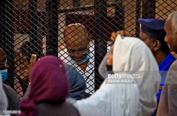 Sudan's ousted president Omar alBashir is greeted by people while inside the defendant's cage during his trial along with 27 coaccused over the 1989...