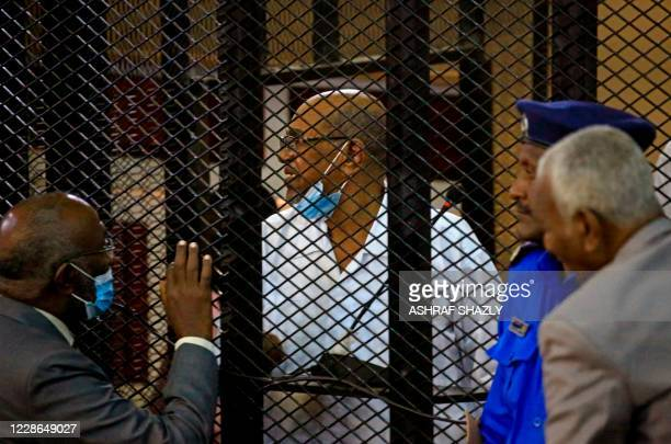 Sudan's ousted president Omar alBashir stands inside the defendant's cage during his trial along with 27 coaccused over the 1989 military coup that...