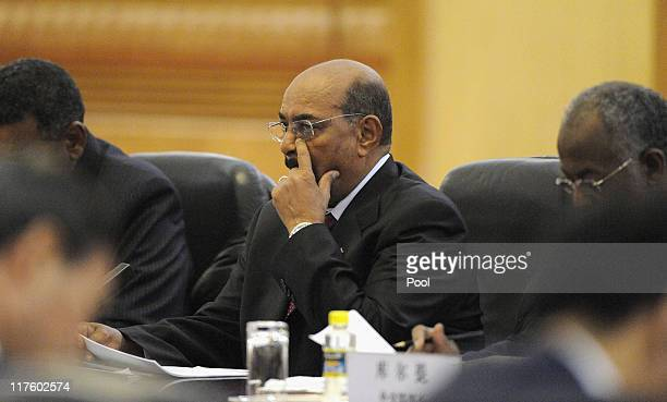Sudan's President Omar al-Bashir talks to Chinese President Hu Jintao during their bilateral meeting at the Great Hall of the People on June 29, 2011...