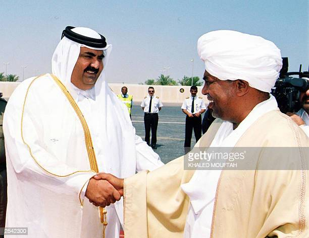 Sudan's President Omar alBeshir is welcomed by Qatar's Sheikh Hamad bin Khalifa alThani upon his arrival 28 September 2003 in Doha Beshir arrived in...