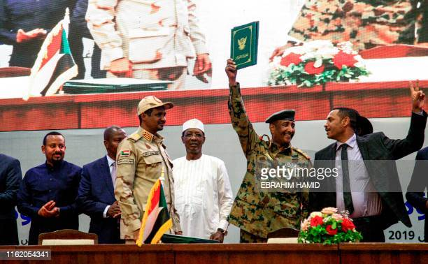 Sudan's protest leader Ahmad Rabie , flashes the victory gesture alongside General Abdel Fattah al-Burhan , the chief of Sudan's ruling Transitional...