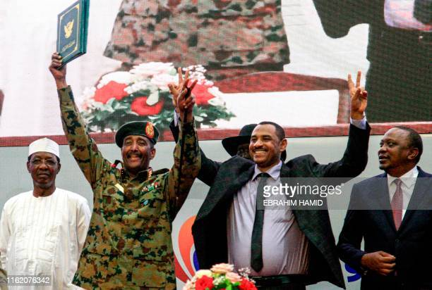 Sudan's protest leader Ahmad Rabie flashes the victory gesture alongside General Abdel Fattah alBurhan the chief of Sudan's ruling Transitional...