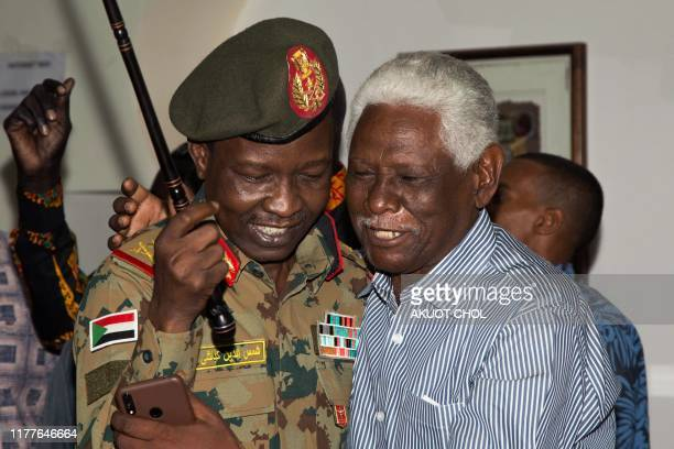 Sudan's ruling Transitional Military Council spokesman and head of Sudan's delegation ShamsEddin Kabashi reacts with a member of Sudan civil society...