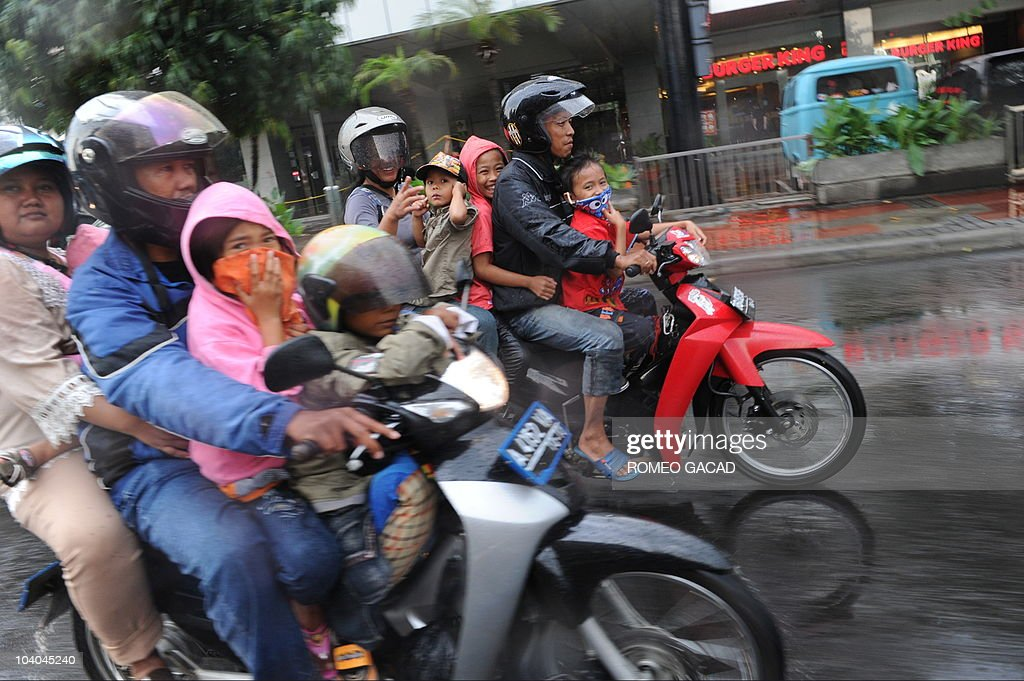 A sudden downpour catches Indonesian families traveling on motorcycle during the Eid al-Fitr holiday in Jakarta on September 11, 2010. Indonesian Muslims are celebrating Eid al-Fitr, the end of the holy month of Ramadan where Muslims observe a strict fast and participate in pious activities such as charitable giving and peace-making. Eid al-Fitr falls on the first day of Shawwal, the month which follows Ramadan in the Islamic calendar. It is a time to give in charity to those in need, and celebrate with family and friends the completion of a month of blessings and joy.