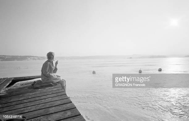 Suède février 1967 L'actrice suédoise Bibi ANDERSSON chez elle Ici l'actrice fumant une cigarette au soleil seule et assise sur un ponton face à la...