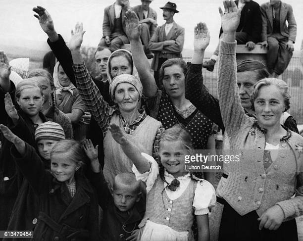 SudetenGermans give the Hitler salute to the Nazi troops as they arrive in Austria 1938