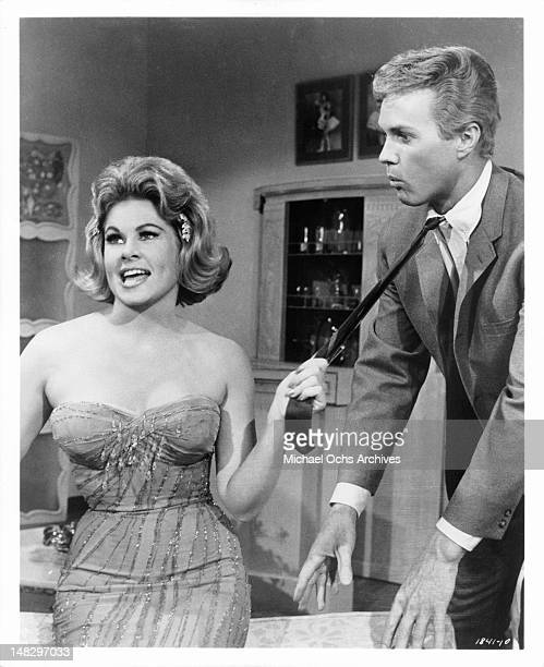 Sue Ane Langdon pulling on the tie of Harve Presnell in a scene from the film 'When The Boys Meet The Girls' 1965