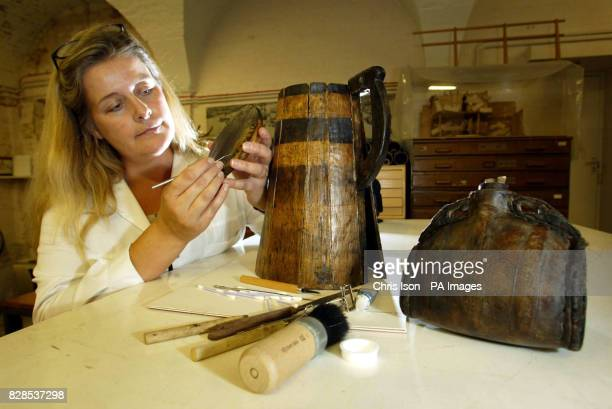 Sue Bickerton Conservator at the Mary Rose Trust works on a mess tankard discovered in mud inside the hulk of the famous Tudor warship in...