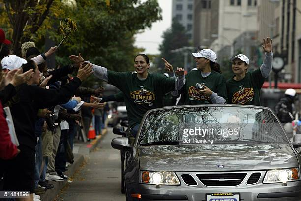Sue Bird greets fans as she rides with teammates Adia Barnes and Tully Bevilaqua during the Seattle Storm victory parade on October 15 2004 in...