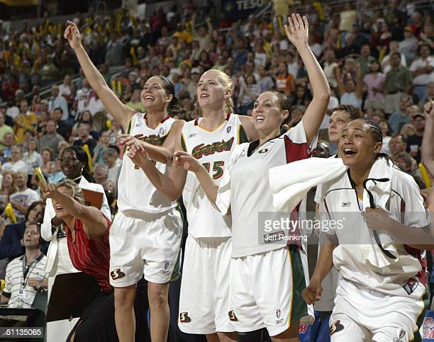 Sue Bird Lauren Jackson Adia Barnes and Betty Lennox of the Seattle Storm from the bench against the Charlotte Sting August 1 2004 at Key Arena in...