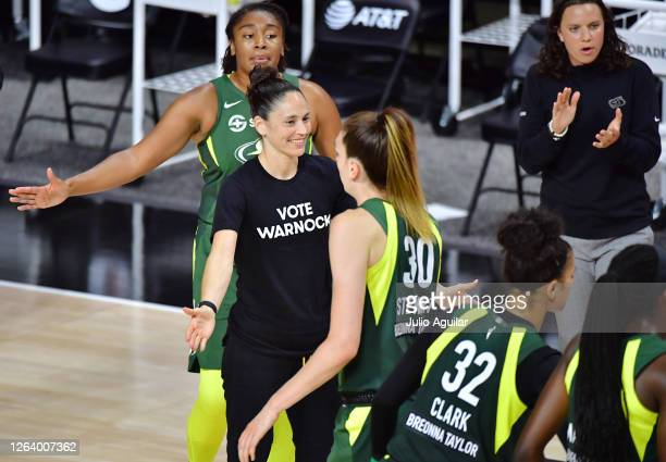 Sue Bird of the Seattle Storm low fives Breanna Stewart while wearing a Vote Warnock T-shirt during the second half of a game against the Connecticut...