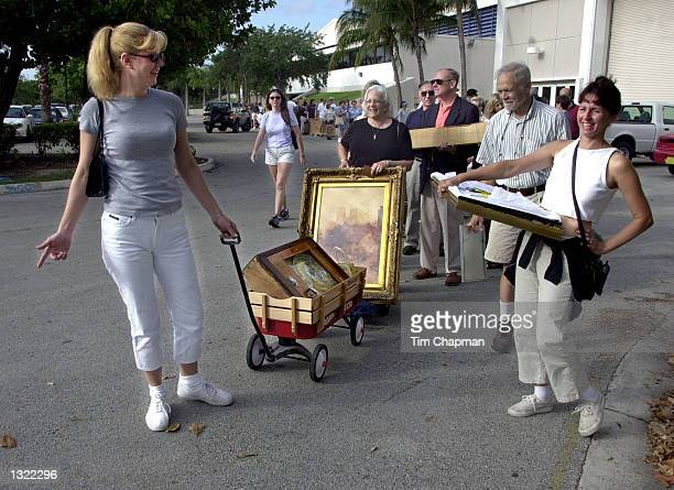 Sue Dale left pulls her son''s wagon with a penny arcade machine from the 1920''s era June 16 2001 while she waits in line to get into Chubb''s...