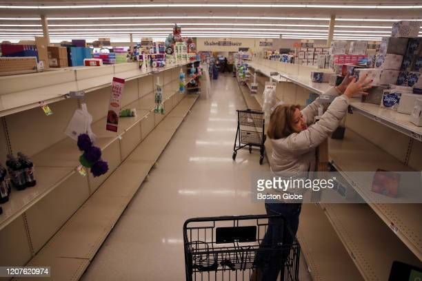 Sue Dauwer of Scituate, MA reaches for boxes of tissue while shopping at Star Market in Marshfield, MA on March 16, 2020. She said she had just...