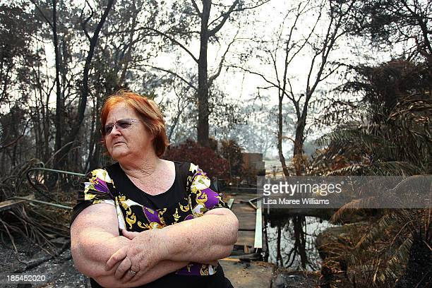 Sue Dunlop sits in the front yard of her home of 41 years which was destroyed by bushfire on October 21 2013 in Winmalee Australia One man has died...
