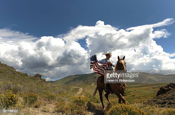 Sue Gaskill raises an American flag on her horse Pawnee while waiting for the peloton to pass by her ranch in between Kremmling and Silverthorne. The...