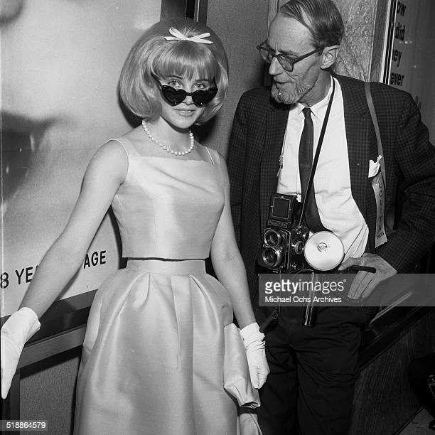 Sue Lyon looks to pose with photographer Earl Leaf as she attends the movie premiere of Lolita in Los AngelesCA