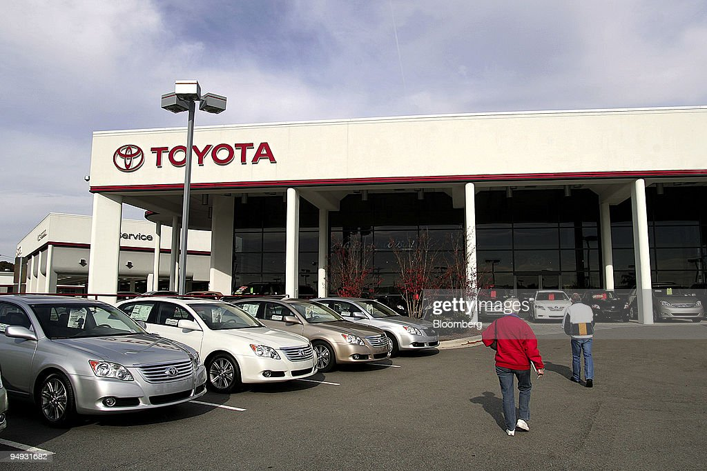 Sue Smith Foreground Walks Past Toyota Vehicles On The Dealership Lot At Mark  Jacobson Toyota In