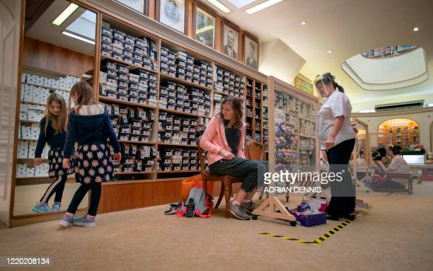 Sue Stamp , manager of the ladies department, watches as a young girl looks in the mirror while trying a new pair of shoes after opening on the first...
